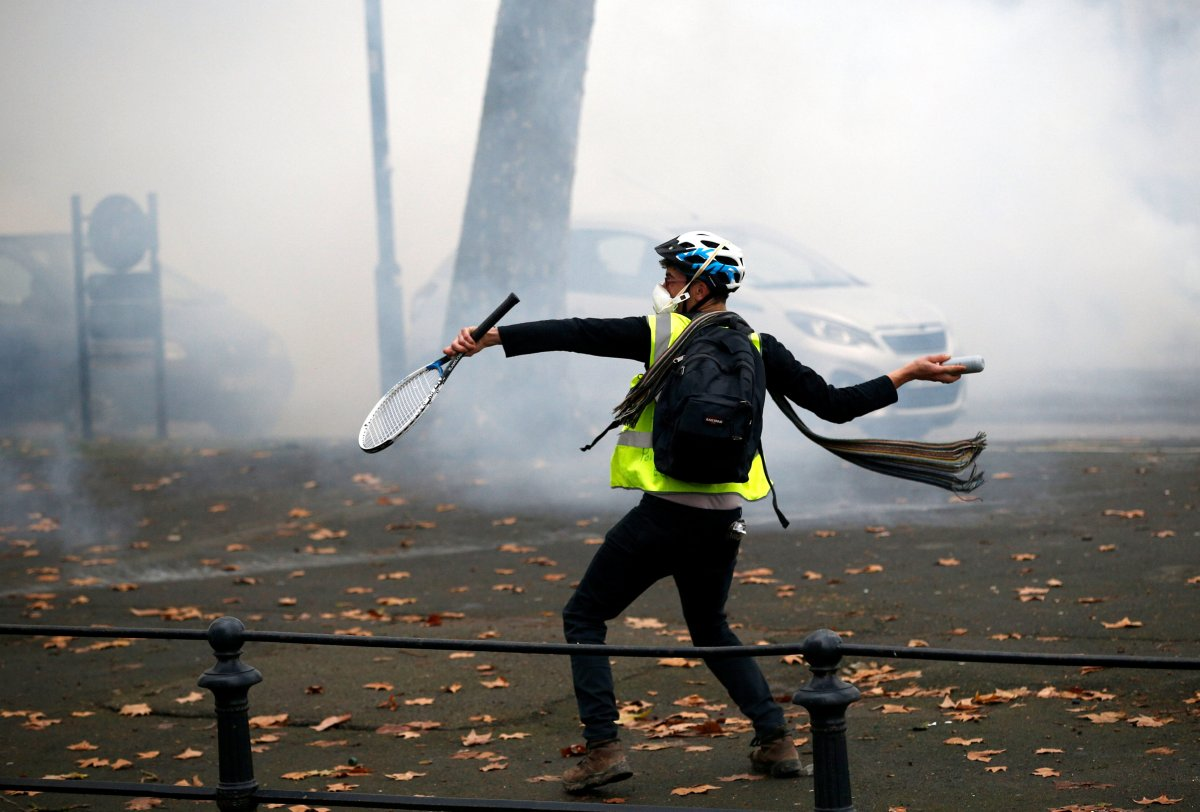"""A protester wearing a yellow vest reacts to the tear-gas canisters fired by police during a demonstration of the """"yellow vests"""" movement in Nantes, France, December 22, 2018. REUTERS/Stephane Mahe."""