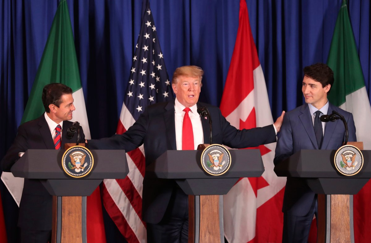 President Donald Trump, center, reaches out to Mexico's President Enrique Pena Nieto, left, and Canada's Prime Minister Justin Trudeau as they prepare to sign a new United States-Mexico-Canada Agreement that is replacing the NAFTA trade deal, during a ceremony at a hotel before the start of the G20 summit in Buenos Aires, Argentina, Friday, Nov. 30, 2018.