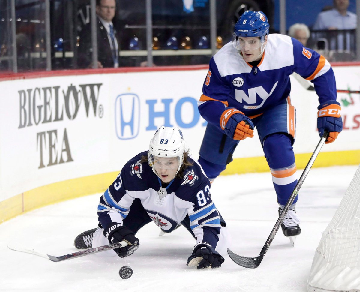 Winnipeg Jets defenseman Sami Niku, bottom, of Finland, loses his footing while trying to control the puck against New York Islanders defenseman Ryan Pulock during the first period of an NHL hockey game, Tuesday, Dec. 4, 2018, in New York. (AP Photo/Julio Cortez).