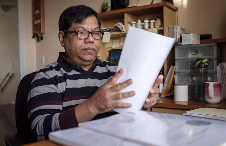 Nalliah Balachandran sorts through some of the legal documents he has accumulated at his home in Calgary, Alta., Tuesday, Dec. 4, 2018.