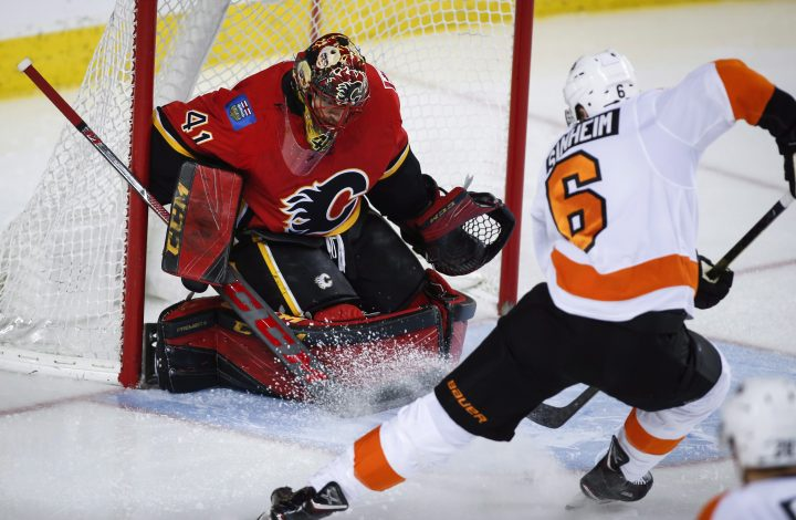 Philadelphia Flyers' Travis Sanheim, right, scores on Calgary Flames goalie Mike Smith during second period NHL hockey action in Calgary, Wednesday, Dec. 12, 2018.