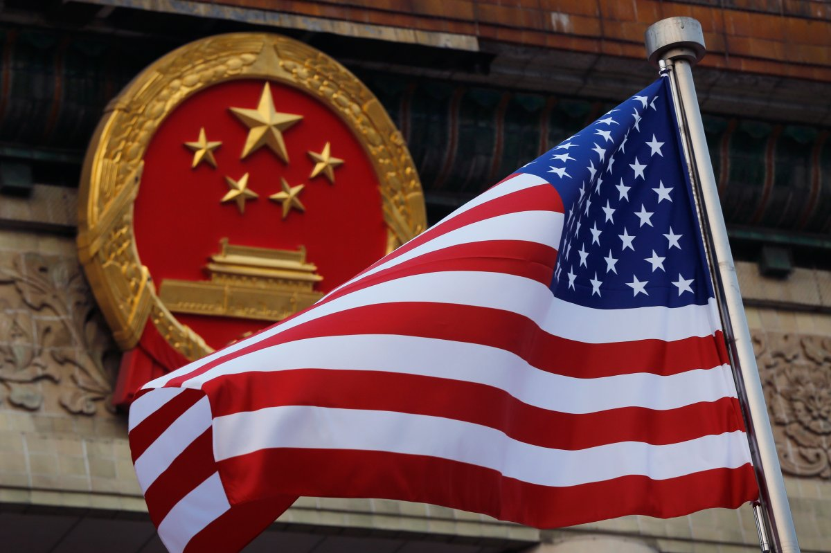 FILE - In this Nov. 9, 2017, file photo, an American flag is flown next to the Chinese national emblem during a welcome ceremony at the Great Hall of the People in Beijing.