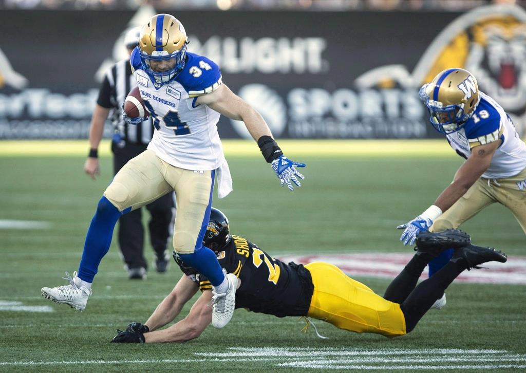 Winnipeg Blue Bombers linebacker Jesse Briggs (34) eludes a tackle by Hamilton Tiger-Cats linebacker Nick Shortill (23) during a faked punt to get a first down during first quarter CFL game action in Hamilton, Ont., on June 29, 2018. The Winnipeg Blue Bombers have signed Canadian linebacker Jesse Briggs to a two-year contract. Briggs was selected 17th overall by Winnipeg in the 2014 CFL draft and has spent the past five seasons with the Bombers. The native of Kelowna, B.C., has appeared in 87 games, tallying 56 special teams tackles and 18 defensive tackles.