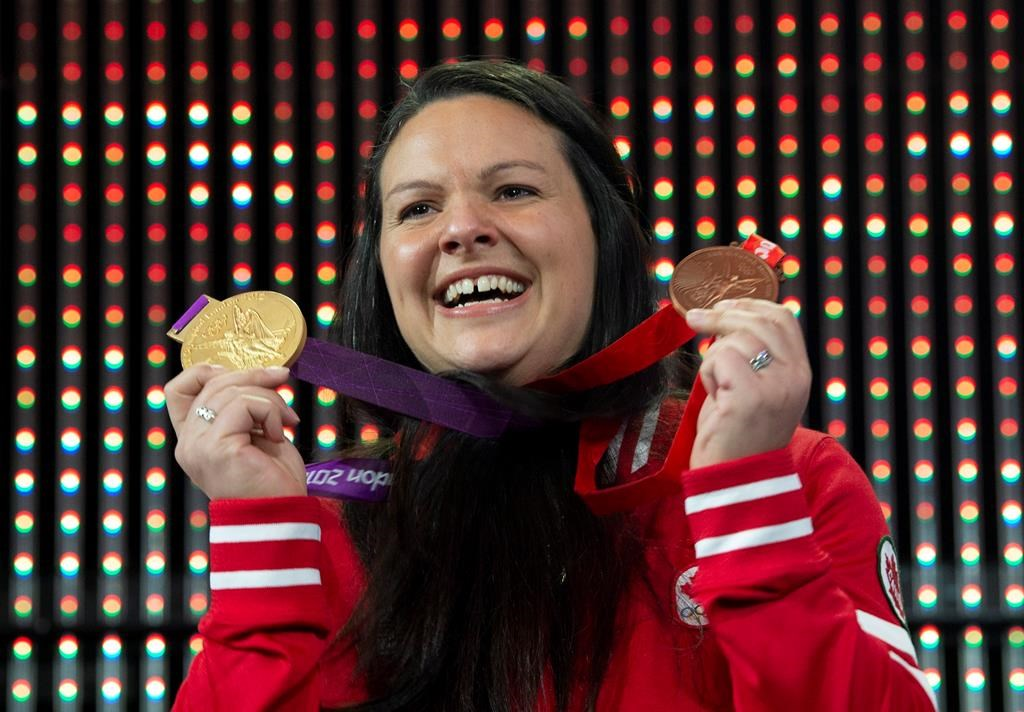 Canadian weightlifter Christine Girard holds up the gold and bronze Olympic medals she was awarded during a ceremony Monday December 3, 2018 in Ottawa. Girard was awarded the London 2012 gold and Beijing 2008 bronze medals after the International Olympic Committee disqualified athletes from the 2008 and 2012 Olympic games.