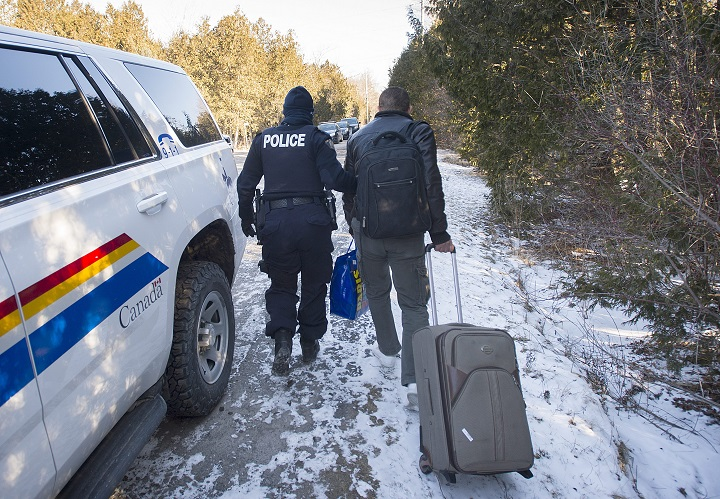 An RCMP officer takes a man into custody after he crossed illegally into Canada from the U.S. on Roxham Road in Hemmingford, Que., Sunday, March 5, 2017.