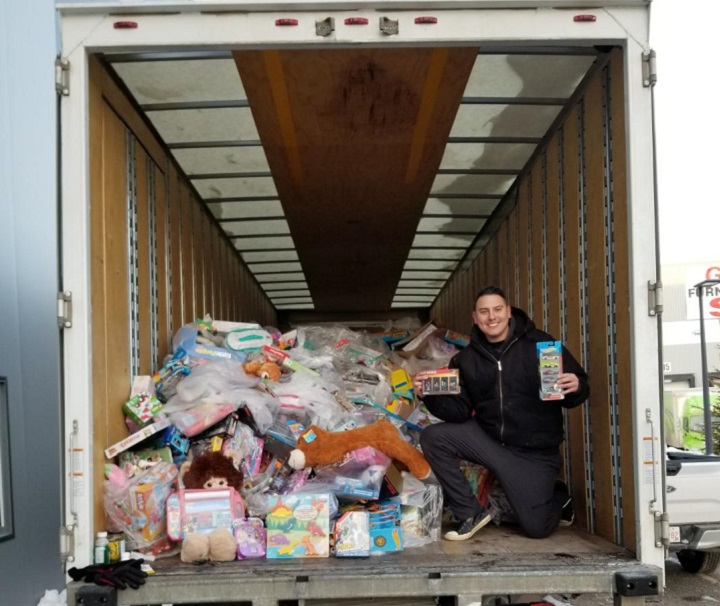 Can Man Dan poses infront of truck full of toys to be donated to 630 CHED Santa's Anonymous.