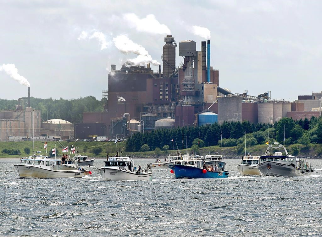 Fishing boats pass the Northern Pulp mill as concerned residents, fishermen and Indigenous groups protest the mill's plan to dump millions of litres of effluent daily into the Northumberland Strait in Pictou, N.S., on Friday, July 6, 2018.