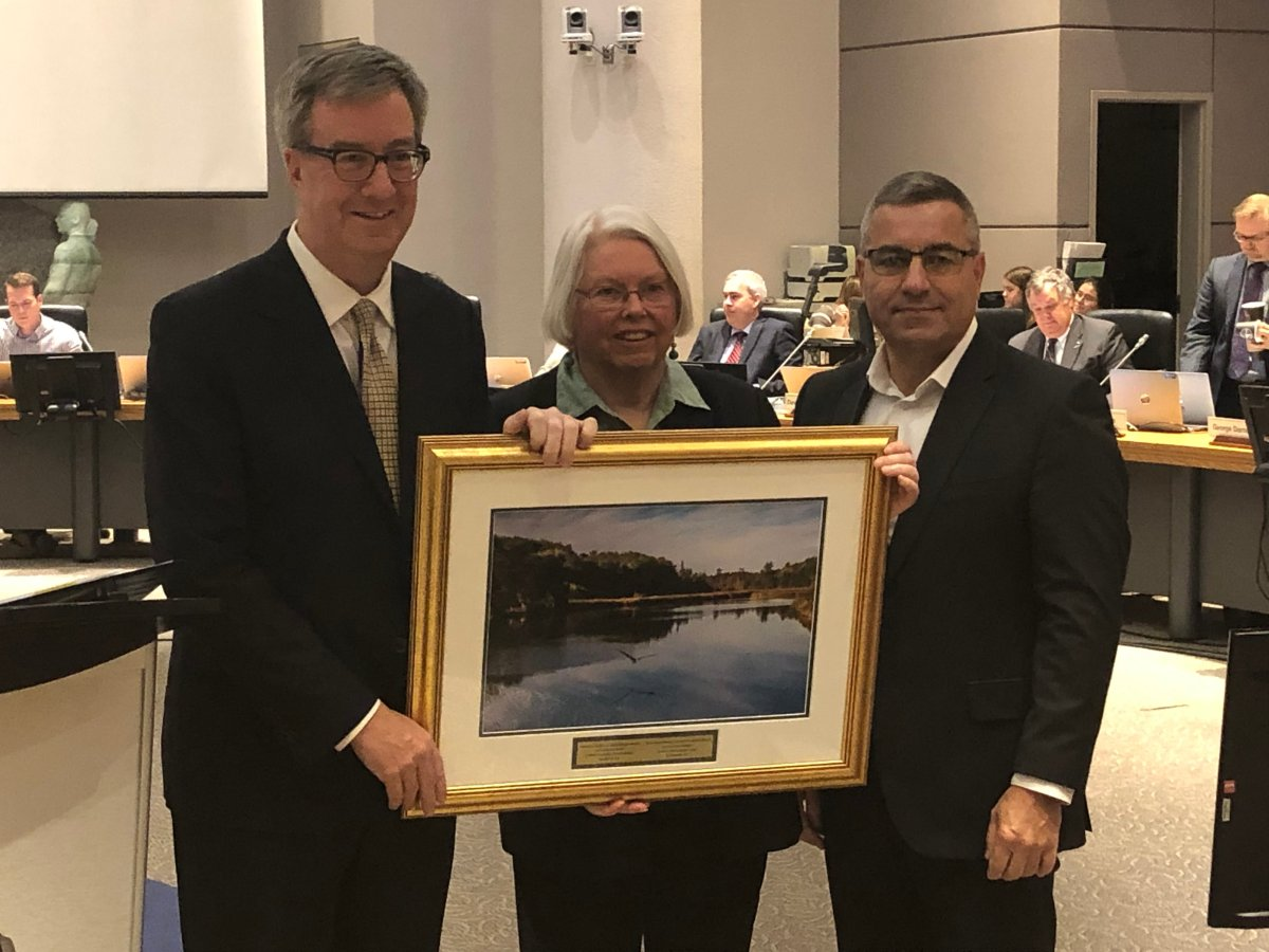 Outgoing Kanata North Councillor Marianne Wilkinson (centre) accepts a photo as a farewell gift from Mayor Jim Watson and city manager Steve Kanellakos at a ceremony before council on Nov. 28.