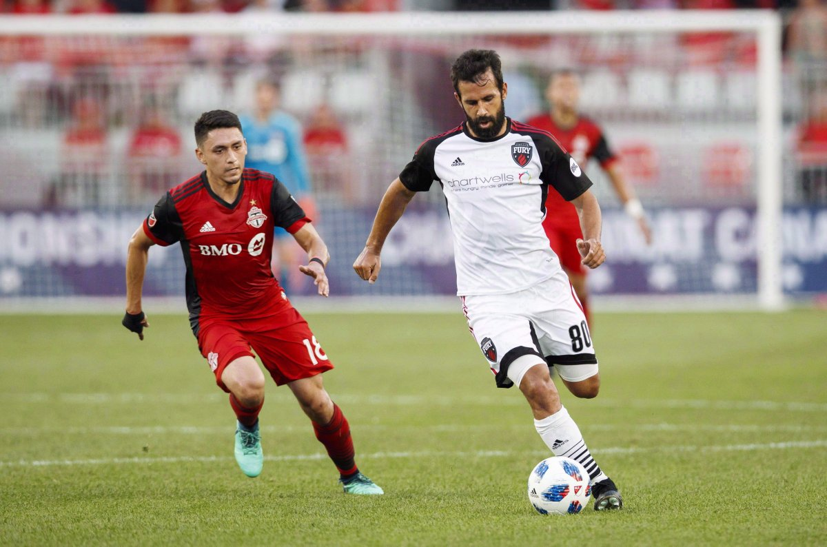 Ottawa Fury FC's Cristian Portilla battles for the ball with Toronto FC's Marco Delgado, left, during the first half of Canadian Championship soccer action in Toronto on July 25, 2018.