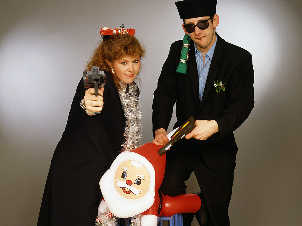 Kirsty MacColl and Shane MacGowan pose with toy guns and an inflatable Santa in a festive scenario, circa 1987.