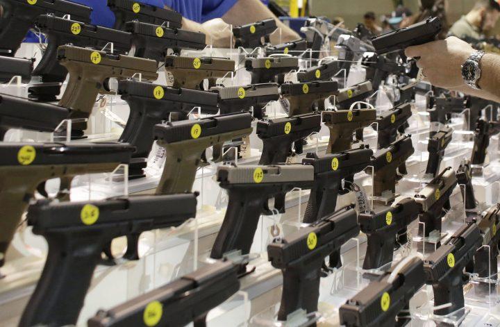 A customer looks at a pistol at a vendor's display at a gun show held by Florida Gun Shows in Miami.