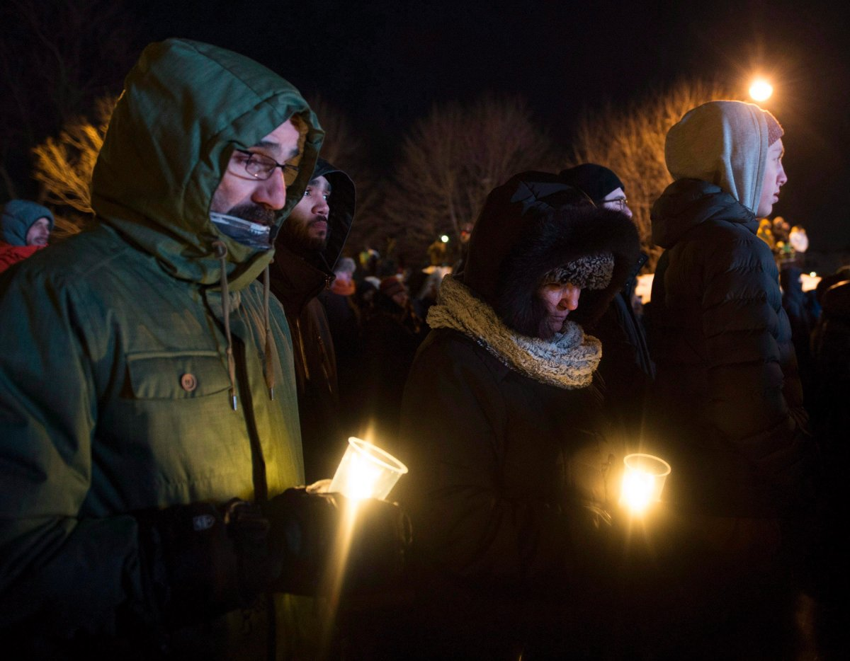 People hold candles at a vigil to commemorate the one-year anniversary of the Quebec City mosque shooting, in Quebec City, Monday, Jan. 29, 2018.