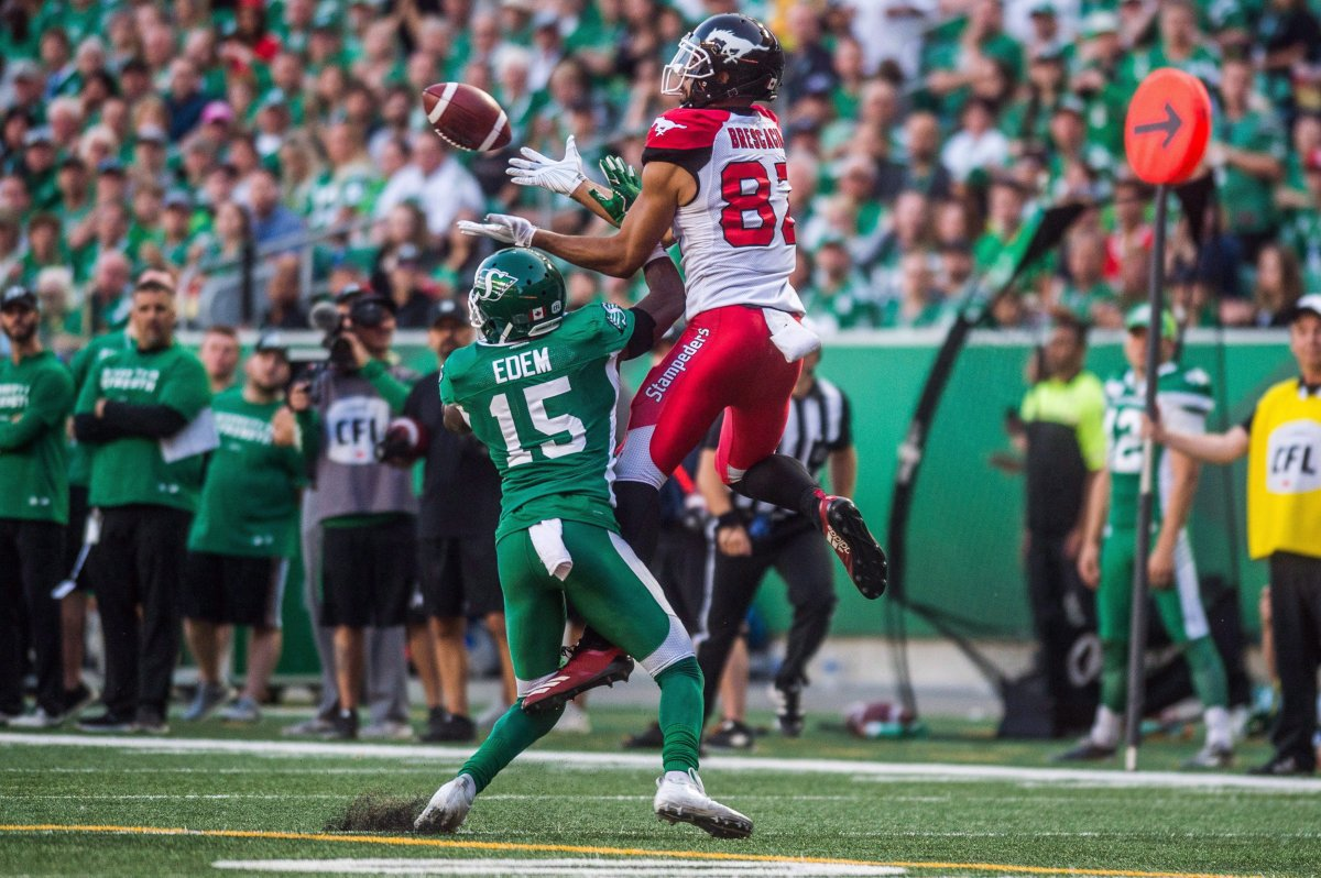 Saskatchewan Roughriders safety Mike Edem (15) tries to block a pass intended for Calgary Stampeders wide receiver Juwan Brescacin (82) during second half CFL action in Regina on Sunday, August 19, 2018. The Saskatchewan Roughriders defeated the Calgary Stampeders 40-27.