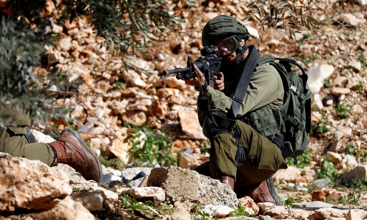 An Israeli soldier aims his weapon during clashes with Palestinians at a protest near Nablus in the Israeli-occupied West Bank January 4, 2019.