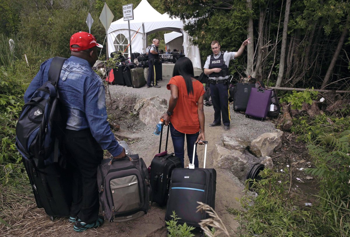 In this Aug. 7, 2017 file photo, an RCMP officer informs a migrant couple of the location of a legal border station, shortly before they illegally crossed from Champlain, N.Y., to Saint-Bernard-de-Lacolle, Quebec, using Roxham Road.