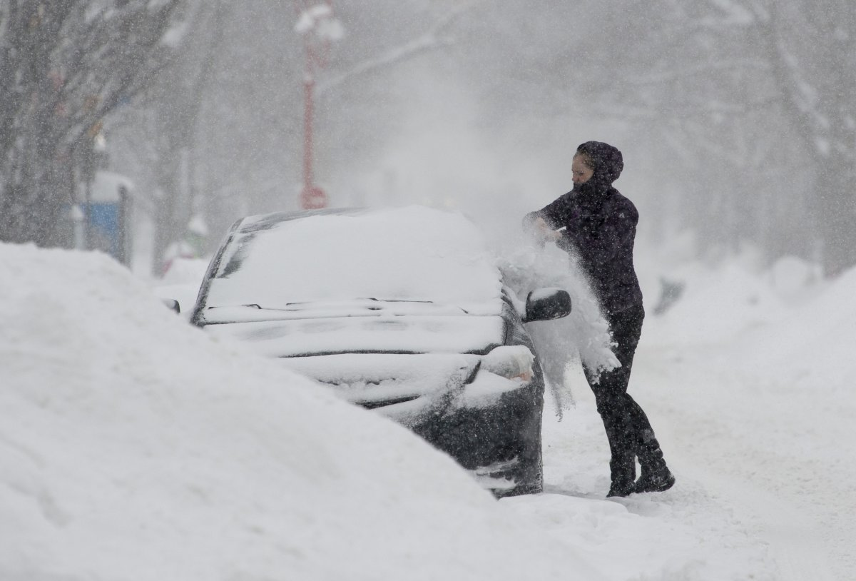 A woman clears snow from her car .