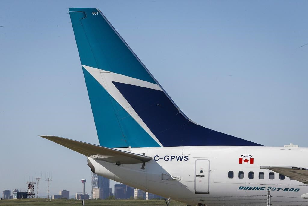 The tail of a WestJet plane is seen dwarfing the Calgary skyline before the airline's annual meeting in Calgary, Tuesday, May 3, 2016.