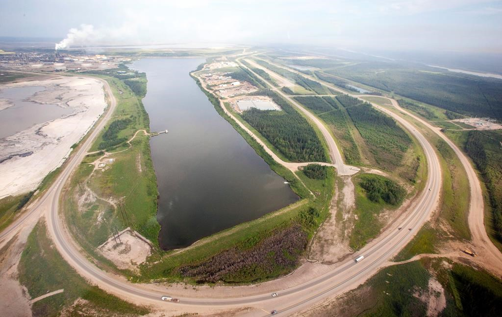 A highway loops around a tailings pond at the Syncrude facility as seen from a helicopter tour of the oil sands near Fort McMurray, Alta., on July 10, 2012.  THE CANADIAN PRESS/Jeff McIntosh.