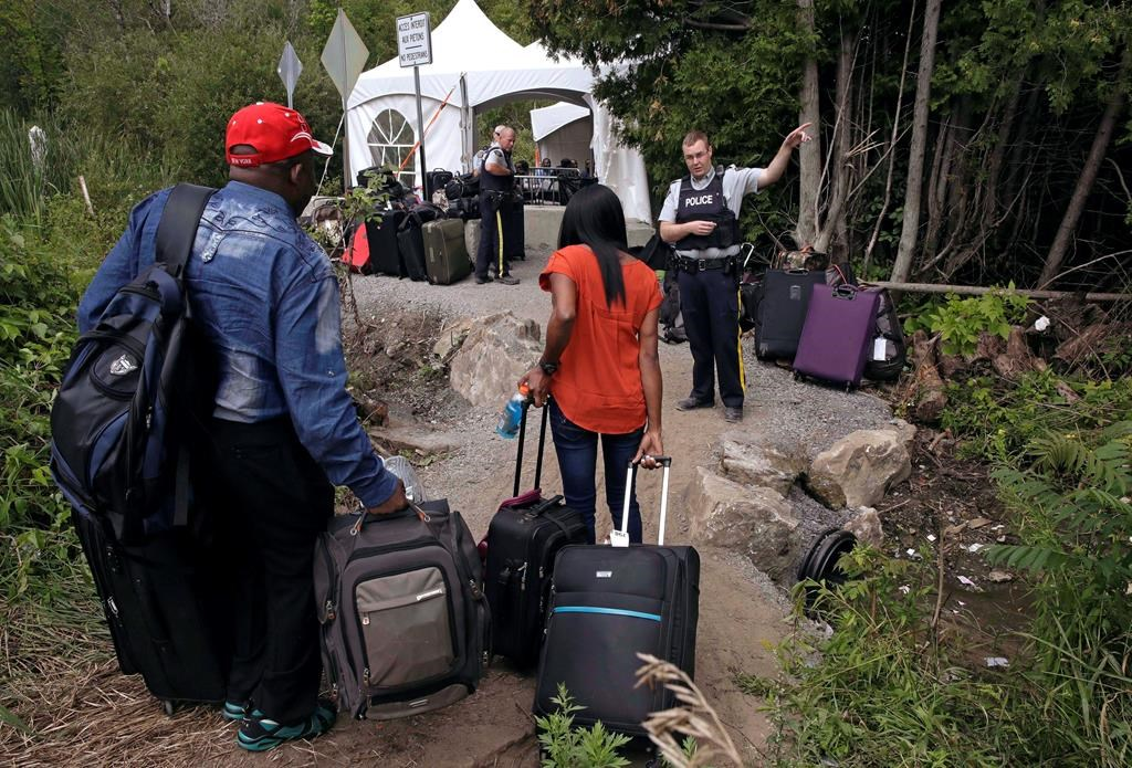 A Royal Canadian Mounted Police officer informs a migrant couple of the location of a legal border station, shortly before they illegally crossed from Champlain, N.Y., to Saint-Bernard-de-Lacolle, Quebec, using Roxham Road on August 7, 2017.