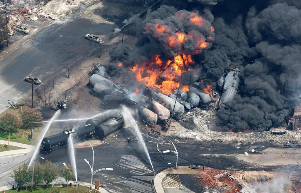 Smoke rises from railway cars that were carrying crude oil after derailing in downtown Lac-Megantic, Que., Saturday, July 6, 2013.