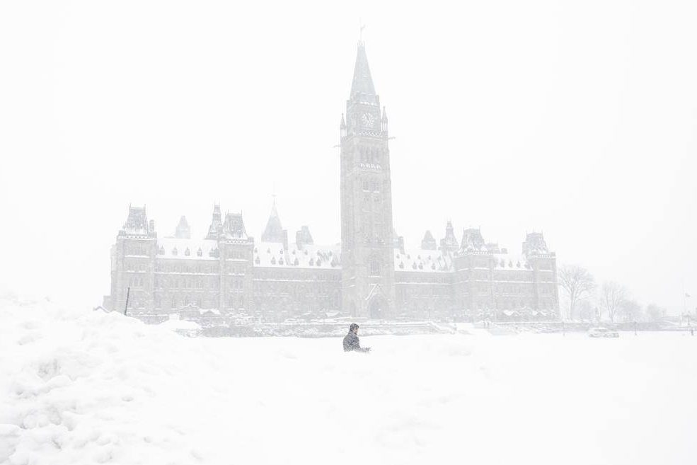 A pedestrian walks past a snowbank on Parliament Hill in Ottawa on Sunday, January 20, 2019.