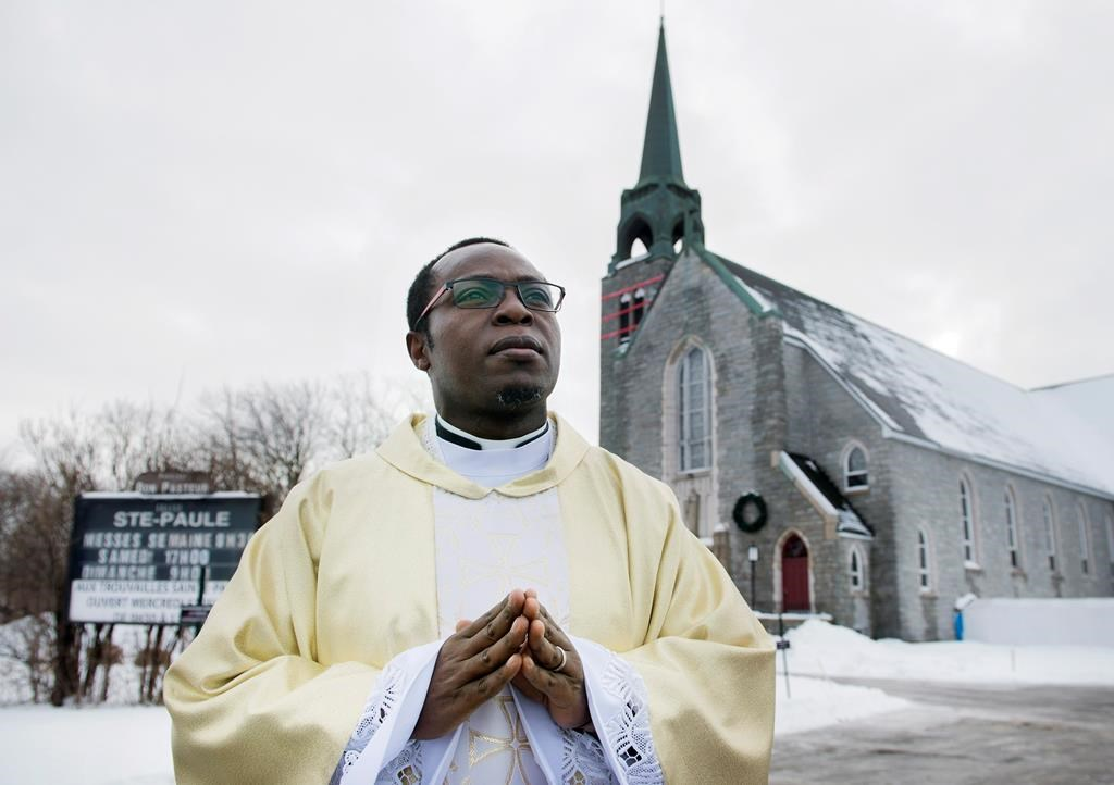 Father Gauthier Elleme poses outside Sainte-Paule's church in Saint-Jerome, Que., Saturday, January 5, 2019.