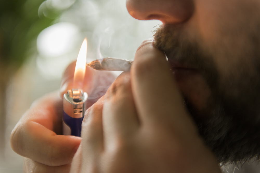 A man lights a joint in this file image.