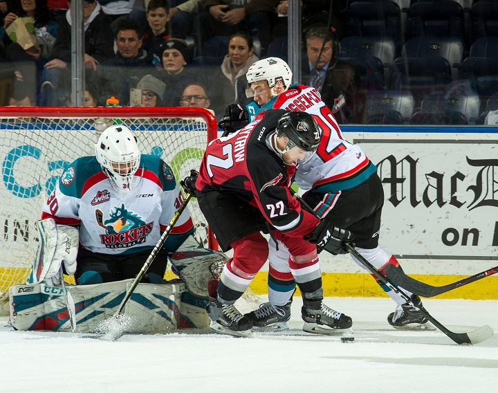 Jared Dmytriw of the Vancouver Giants, middle, looks for the puck as does Kelowna goaltender Roman Basran while Rockets forward Conner Bruggen-Cate closes in during WHL action in Kelowna on Saturday night.