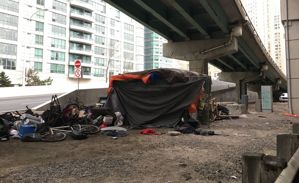 A person's tent and belongings can be seen under an on-ramp to the Gardiner Expressway in downtown Toronto.