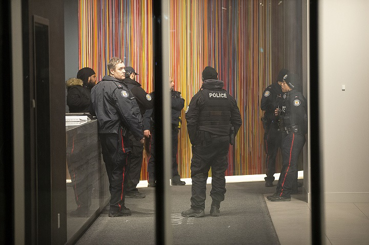 Toronto police officers inside of the lobby of an apartment building near Fort York Friday evening after a shooting in the area left a man with serious injuries.
