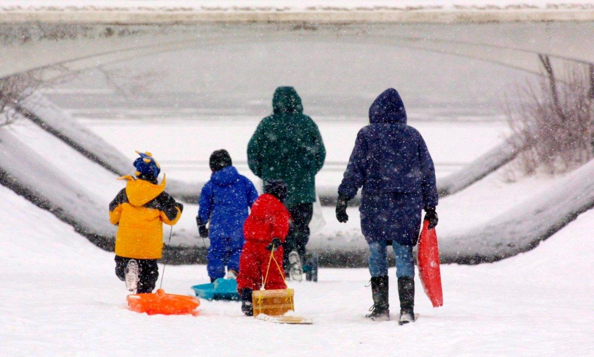 A family makes their way through the freshly fallen snow to go tobogganing.