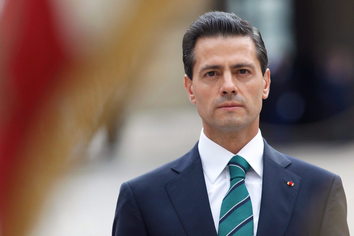 Mexico's then-president Enrique Pena Nieto observes the French flag during a welcoming ceremony, in Paris, Monday, July 13, 2015.