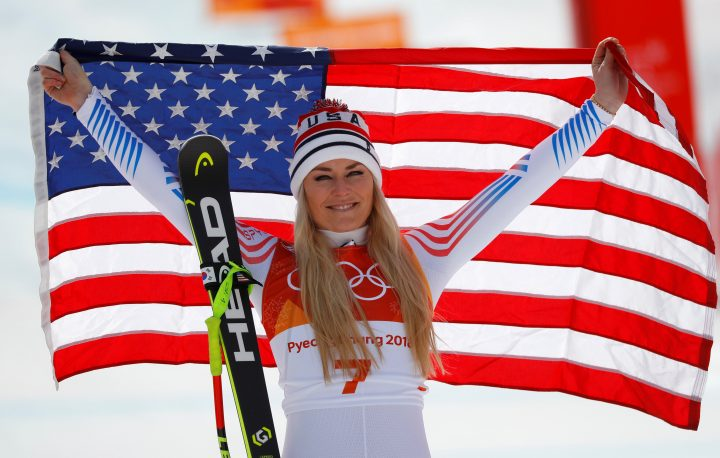 Lindsey Vonn of the U.S. celebrates with a flag during the Olympic flower ceremony.