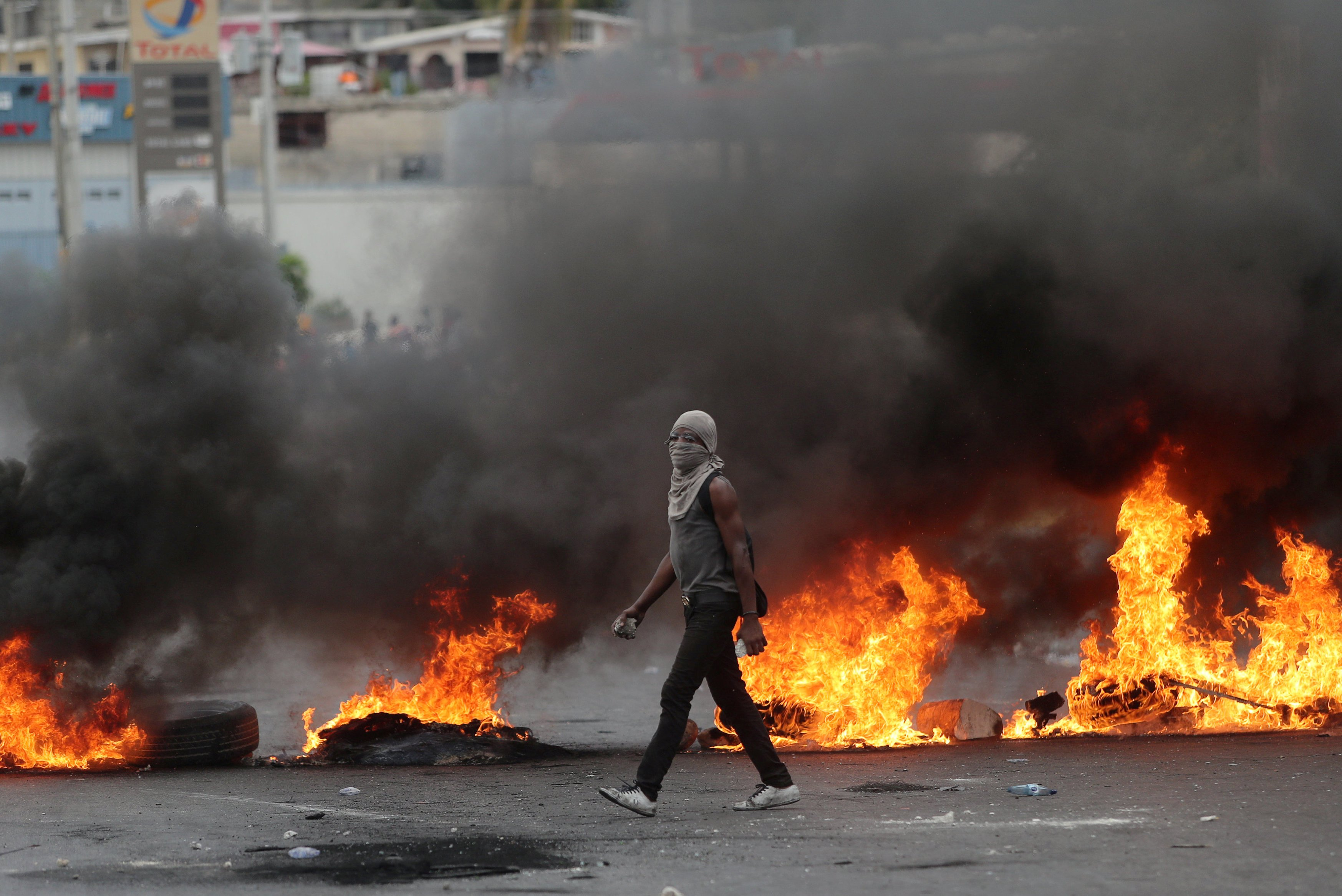FILE – A demonstrator walks past a burning barricade during anti-government protests in Port-au-Prince, Haiti, Feb. 15, 2019.