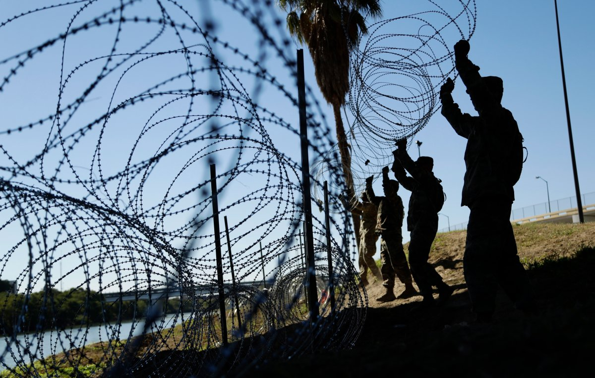 FILE - In this Nov. 16, 2018, file photo, members of the U.S. military install multiple tiers of concertina wire along the banks of the Rio Grande near the Juarez-Lincoln Bridge at the U.S.-Mexico border in Laredo, Texas.