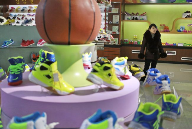 A guide stands near a basketball shoe display in a product exhibition room at the Ryuwon Shoe Factory that specializes in sports footwear, in Pyongyang, North Korea, Feb. 1, 2019.