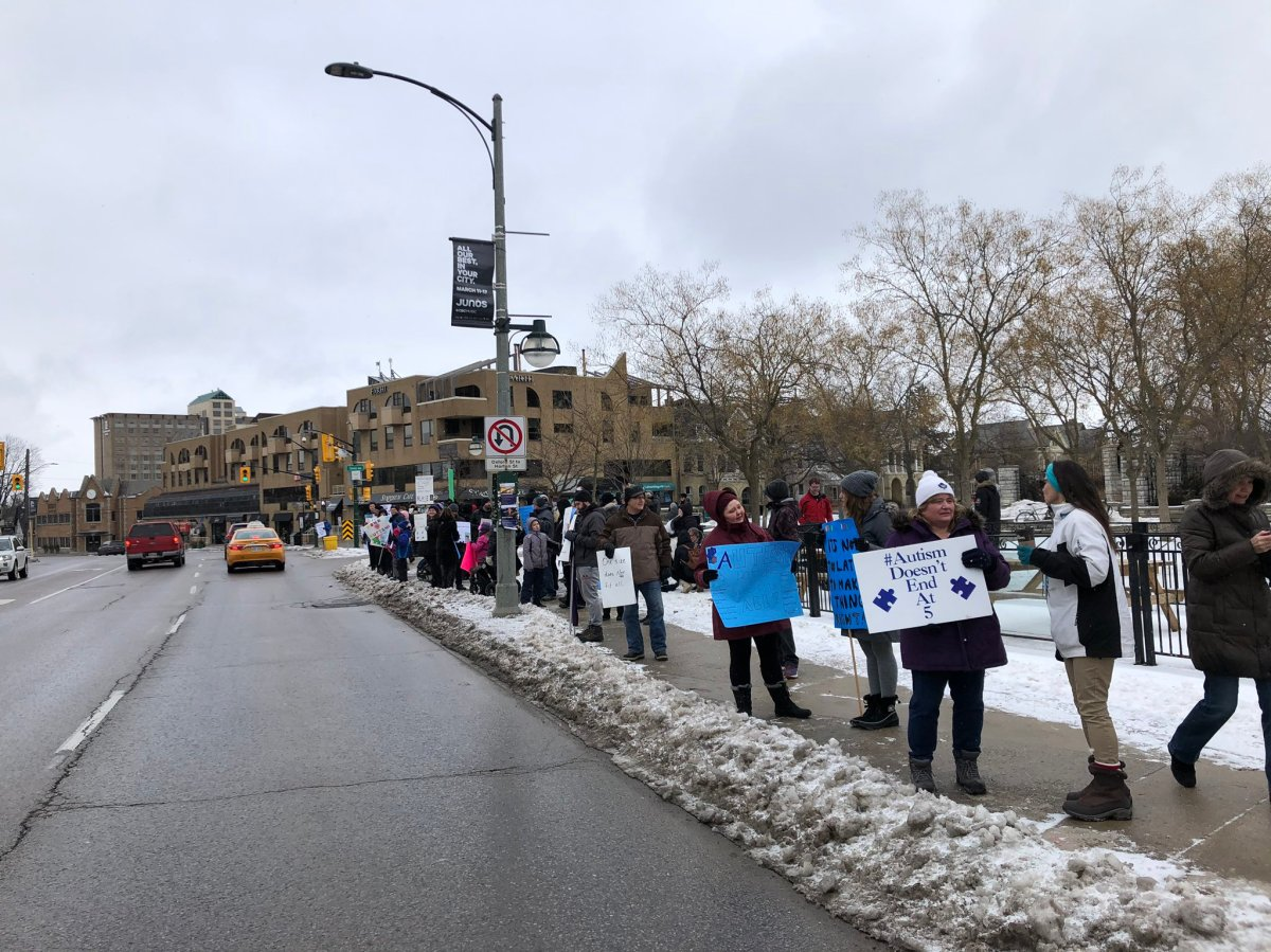 Local parents and community members line up along Richmond Street at the northwest corner of Victoria Park to rally against the Ontario government's changes to the provincial autism program.