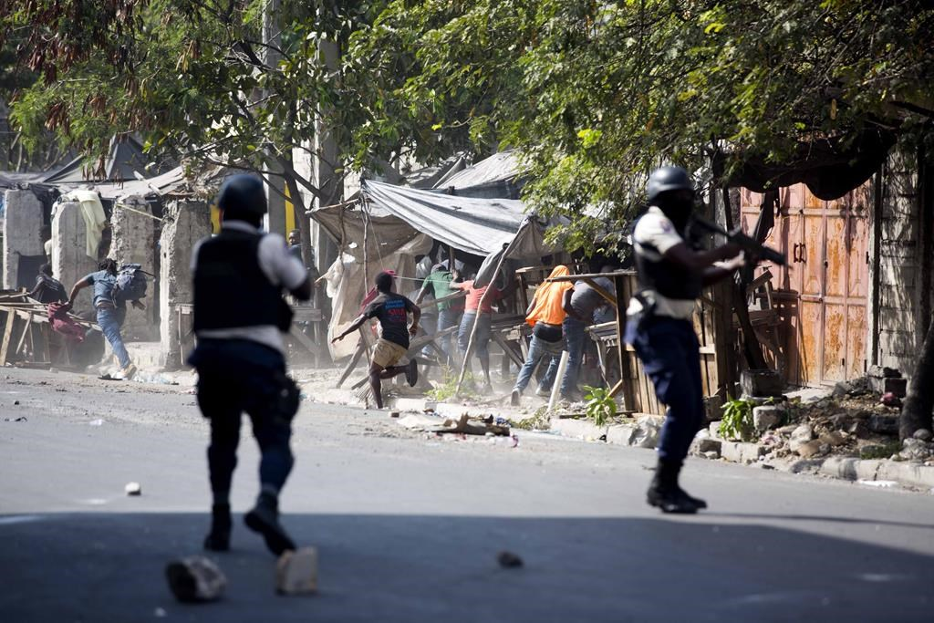 National police shoot at protesters demanding the resignation of Haitian President Jovenel Moise near the presidential palace in Port-au-Prince, Haiti, Wednesday, Feb. 13, 2019. THE CANADIAN PRESS/AP, Dieu Nalio Chery