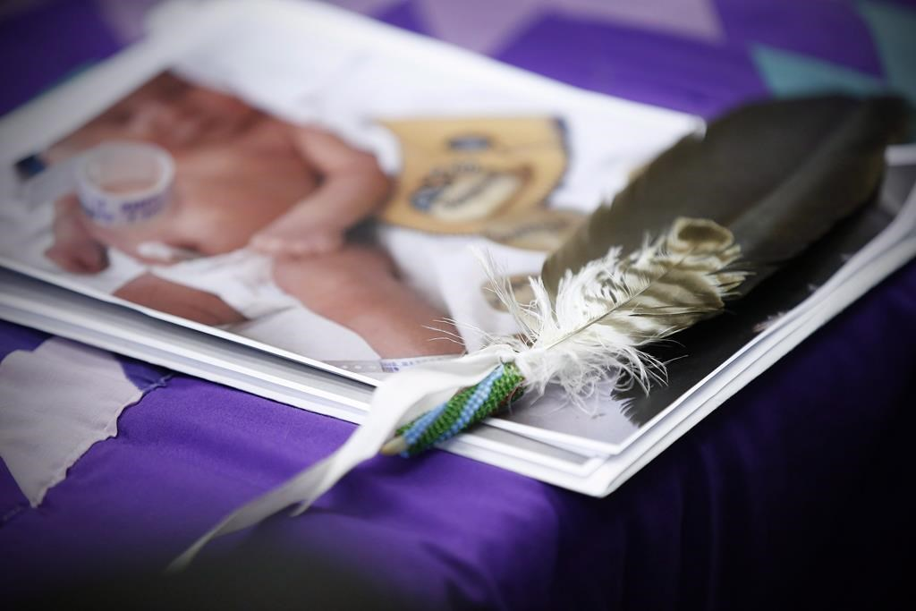 An eagle feather and a baby hospital ID bracelet sit on a photo of a newborn baby during a press conference.