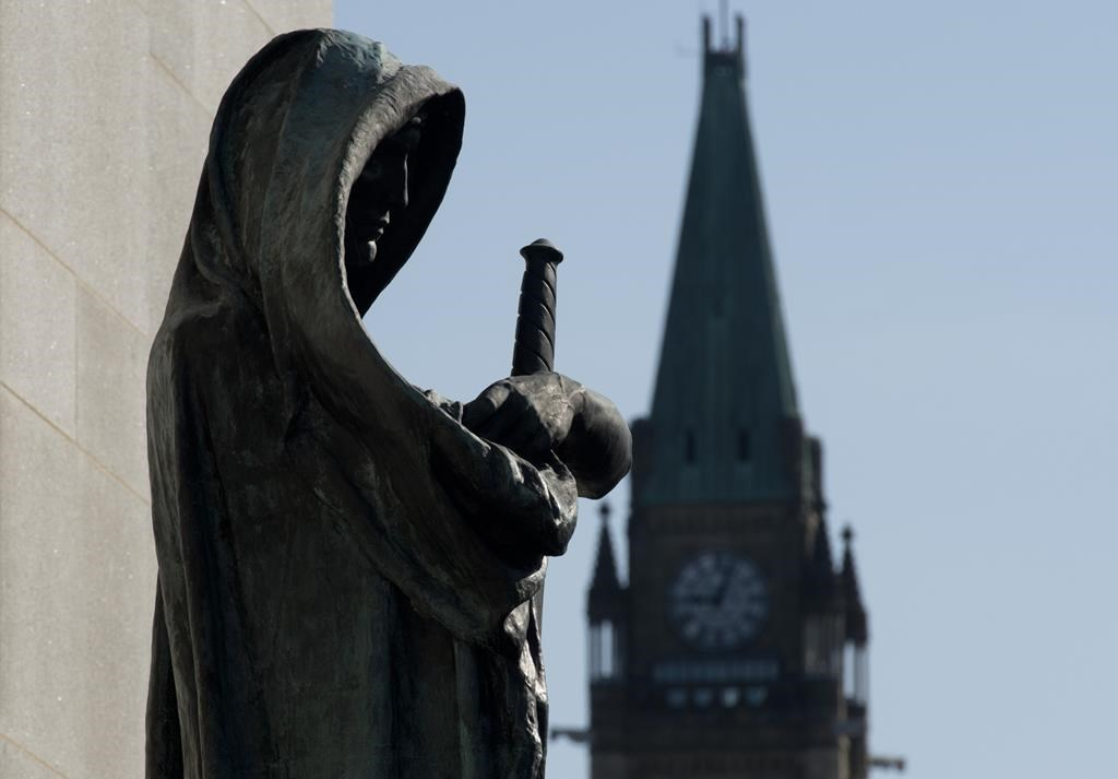 Veritas (Truth) guards the entrance of the Supreme Court of Canada as the Peace tower is seen in the background in an April 25, 2014 photo in Ottawa. The Supreme Court of Canada says an Ontario high-school teacher who used a pen camera to surreptitiously take videos of female students is guilty of voyeurism. Teacher Ryan Jarvis was charged with voyeurism after discovery of more than two dozen videos on his pen, many of which focused on the chests and cleavage area of students at the London, Ont., school.