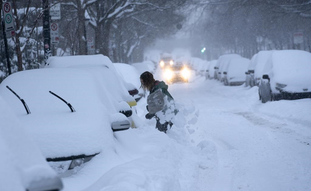 A woman digs her car out of a snowbank during a winter storm in Montreal on Wednesday, Feb. 13, 2019.