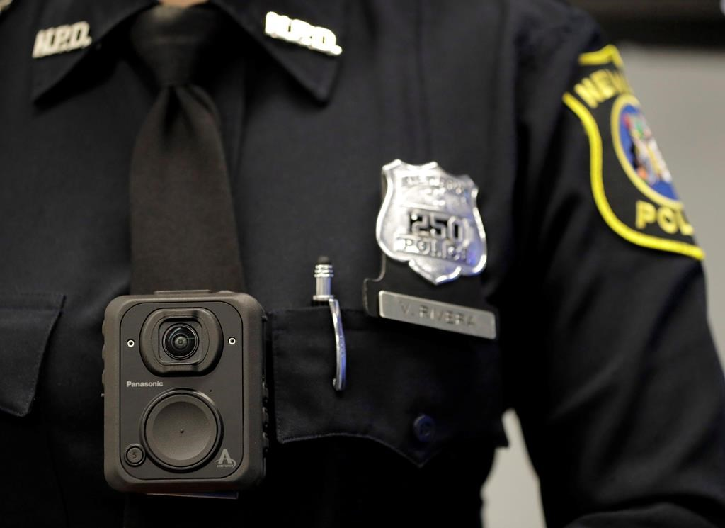 Newark police officer Veronica Rivera displays how a body cam is worn during a news conference unveiling the department's new cameras at the Panasonic headquarters in Newark, N.J., Wednesday, April 26, 2017.