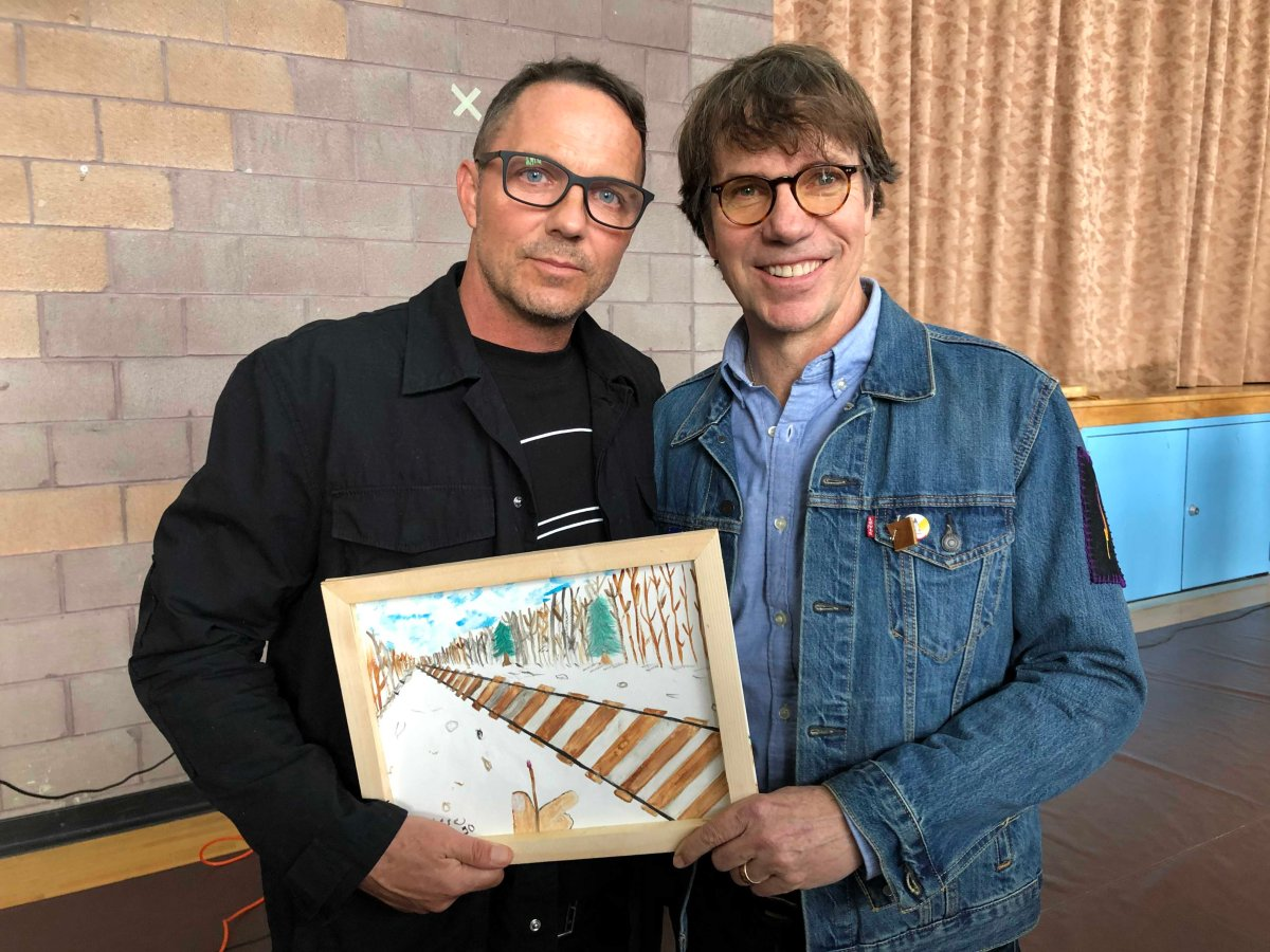 Patrick (left) and Mike Downie pose with a drawing that was gifted to them at Antler River Elementary School in Chippewas of the Thames First Nation.