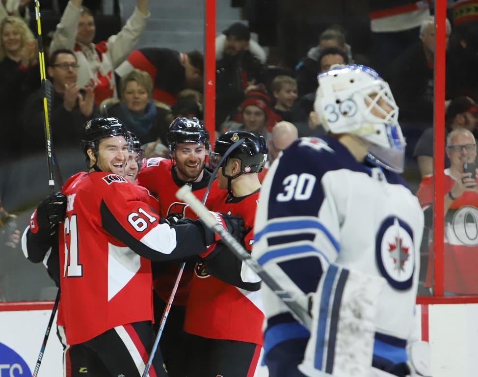 Ottawa Senators right wing Mark Stone (61) celebrates his goal with teammates Ben Harpur (67) and Mark Borowiecki (74) as Winnipeg Jets goaltender Laurent Brossoit (30) looks on during first period NHL hockey action in Ottawa on Saturday, February 9, 2019. THE CANADIAN PRESS/Fred Chartrand.