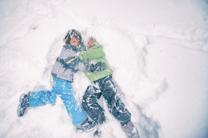 Two children wrestle playfully in the powdery snow during a storm.