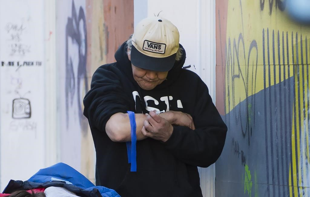 A man injects drugs in Vancouver's Downtown Eastside, Wednesday, Feb. 6, 2019.