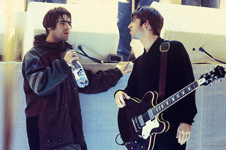 (L-R) Brothers Liam and Noel Gallagher of Oasis talking on the set of a U.K. TV show. (File photo).