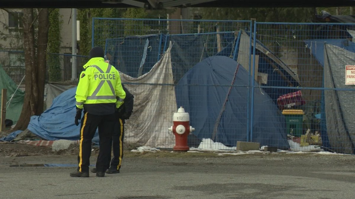 Police stand outside the Maple Ridge homeless camp known as Anita's Place on Sunday, where the city was enforcing a court injunction.