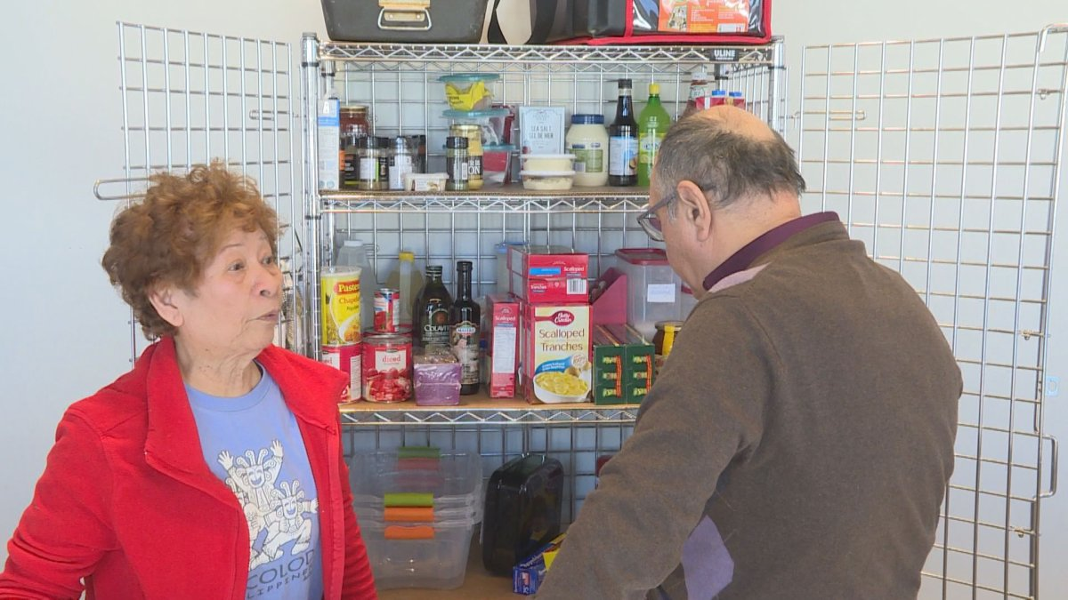 Volunteers examine food in a cabinet at the new meals on wheels kitchen in DDO, set up by Volunteer West Island at the DDO civic Centre.  (Global News).