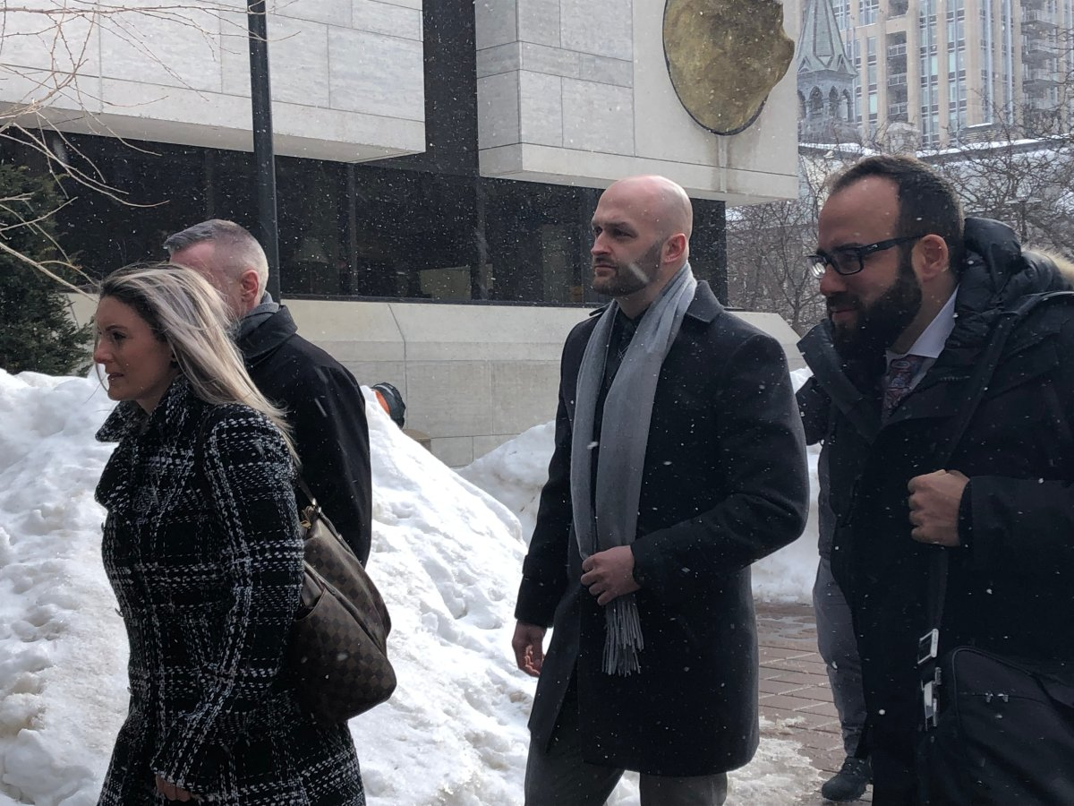 Const. Daniel Montsion (centre) arrives with his defence lawyer, Solomon Friedman (right), at the Ottawa courthouse on Elgin Street on Feb. 25, 2019.